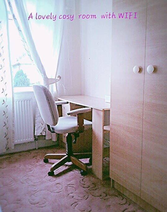 A cosy single room with desk, chair and wardrobe