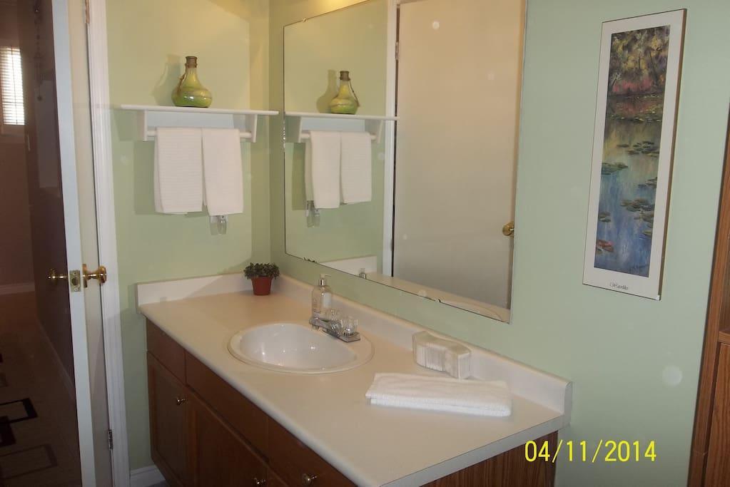 Bright three piece bathroom leads to  bedroom #1