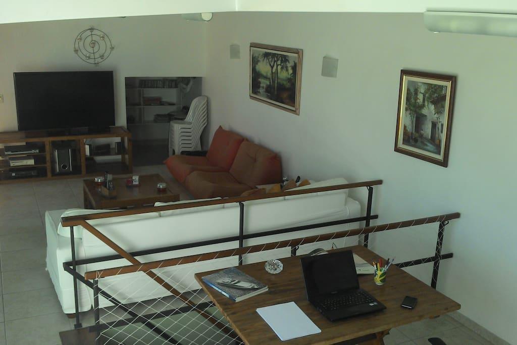 Salas com TV, sofas e amplo espaço para trabalho e lazer