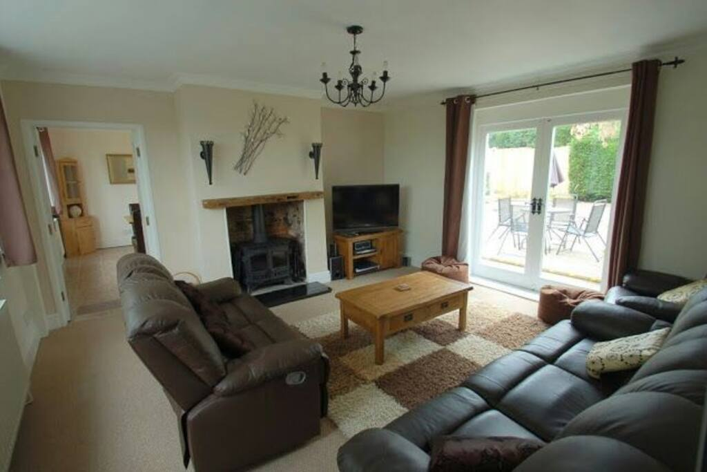Comfy living room with two sofas, a chair, bean bags and tub chairs. Sky HD TV with catch-up and surround sound