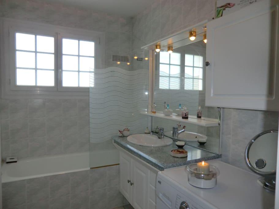Salle de bains privative avec baignoire, une vasque et un lave-linge.