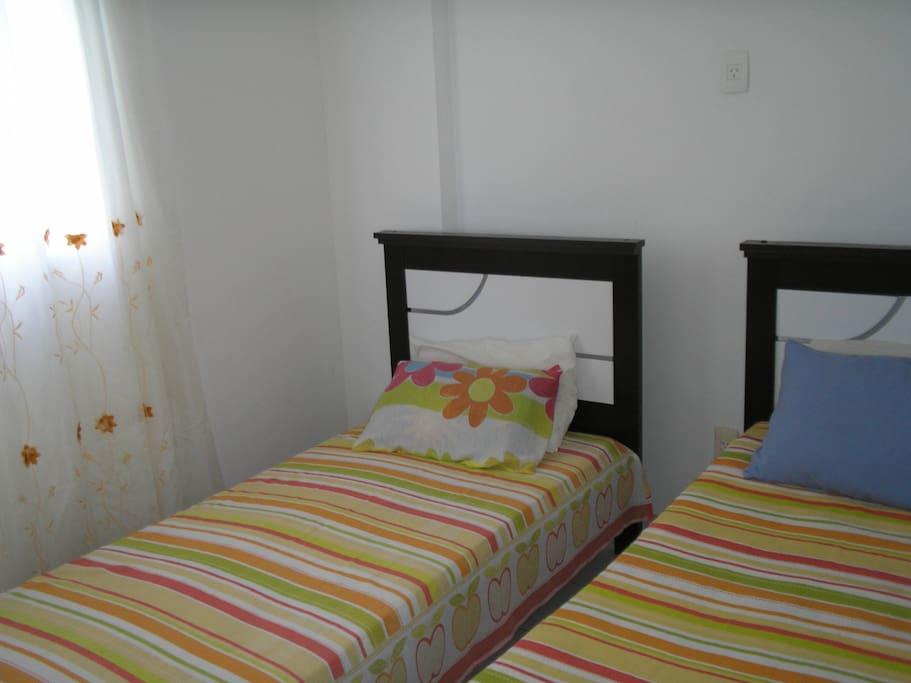 Vista de um dos quartos com camas separadas.