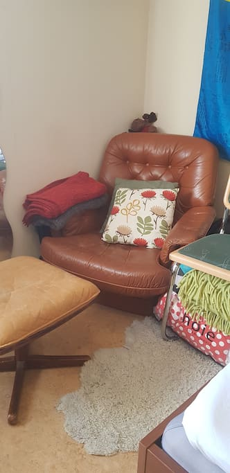 In the corner, there is a cosy armchair next to a lamp, perfect for reading.