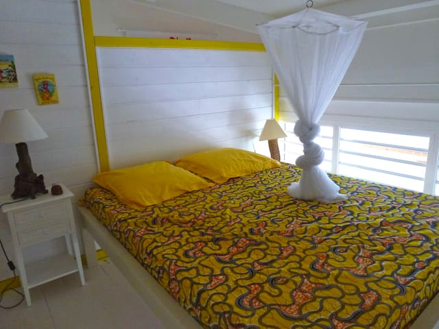 chambre 1 , lit en 160 fermée,avec climatisation  et moustiquaire . lit  160,  du fond  du lit,  vue sur le lagon  tous les matins....miroir, penderie, étagères, 2 tables de nuit avec lampe de chevet, climatisation et moustiquaire, réveil.