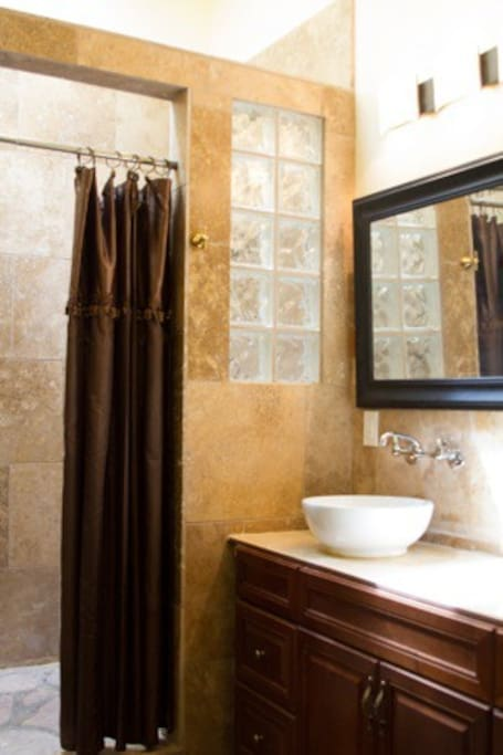 Master bathroom:  double sinks and large double shower with travertine and river rock floor.