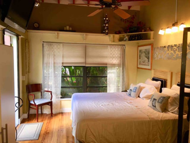 Bedroom from kitchenette, showing large windows and oak wood floors.