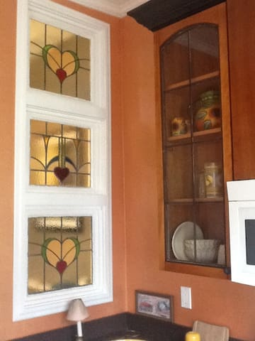Three stained glass windows from Ireland and antique glass doors on custom cabinetry.