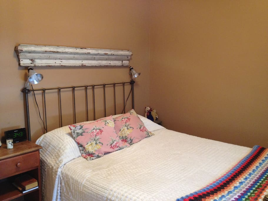 Bed has two reading lamps attached and two bedside tables.