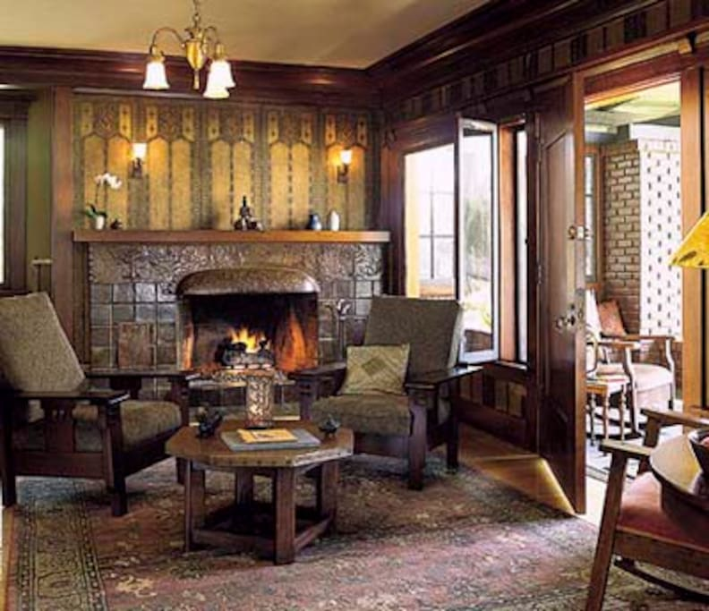 Restored arts and crafts living room with original 1911 wallpaper and Batchelder tile fireplace with hammered copper hood.