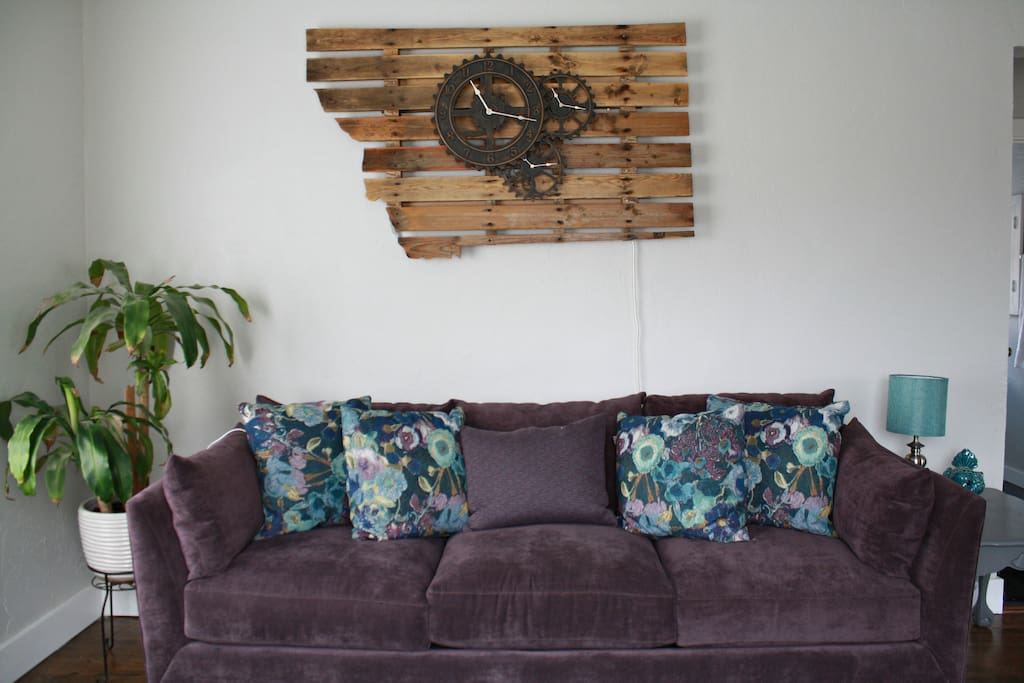 Very cool, hand made,  light up Montana pallet sign above the comfy purple couch.