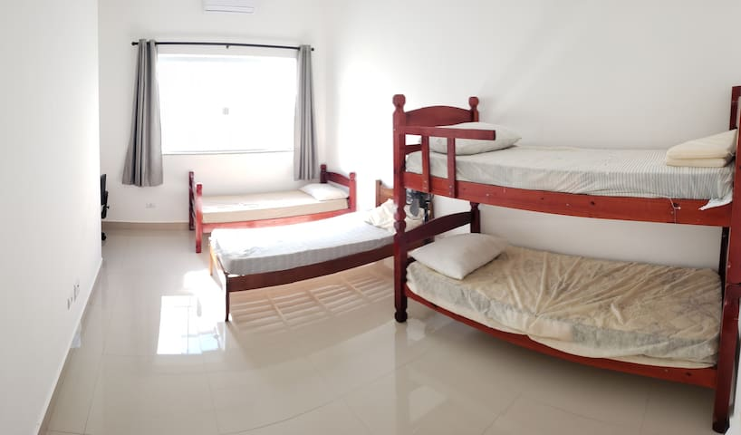 Quanto 2 - Conta com 2 camas de solteiro, um beliche e uma bancada de trabalho.