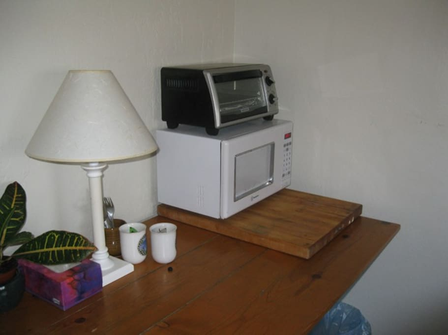 There is a toaster oven, microwave and a fridge in the closet. There is a different desk in the room now.