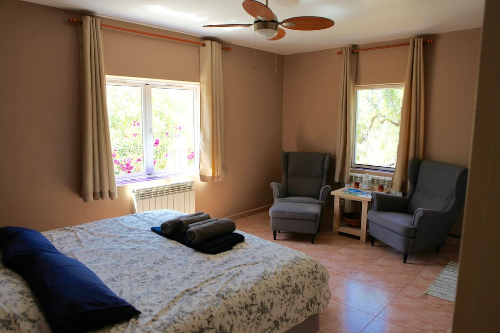 Room 1, with a kingsize bed, two arm chairs, private bathroom and two windows