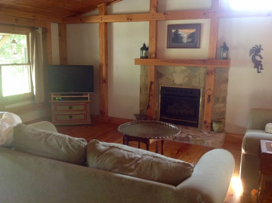 Spacious living room with flatscreen TV and gas fireplace.
