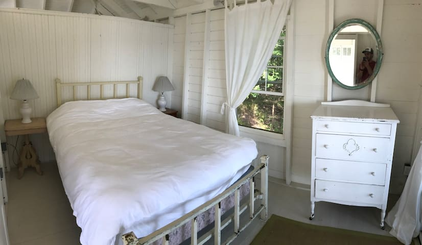 Bright queen bedroom overlooking the ocean, with slider doors leading out to the outdoor dining room.