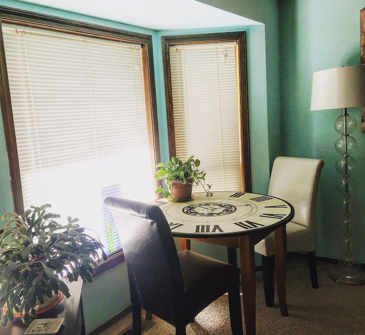 Main living space with table and lounging area, plus some kitchen amenities.