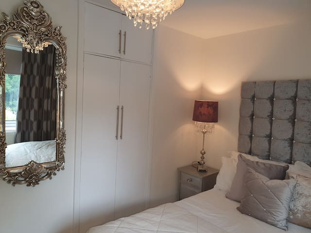 Double bed, bedside cabinet, built in wardrobe and long mirror
