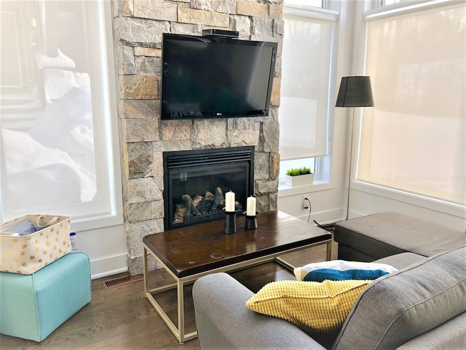 Wall mount TV, fireplace, and an ottoman for an extra seating