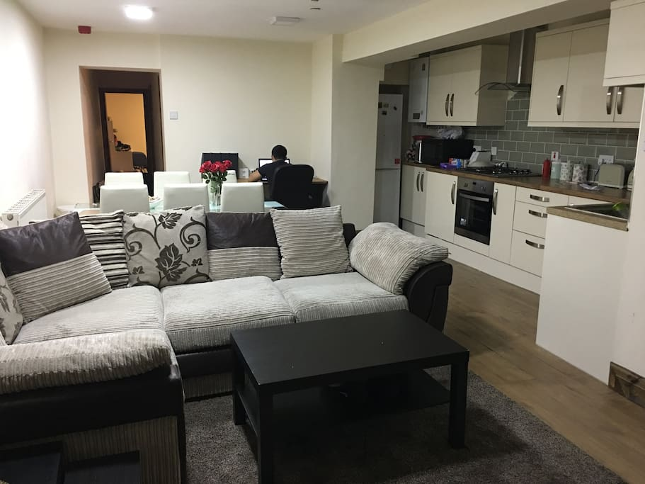Living room with an open kitchen. Includes couch, dining table and study table.