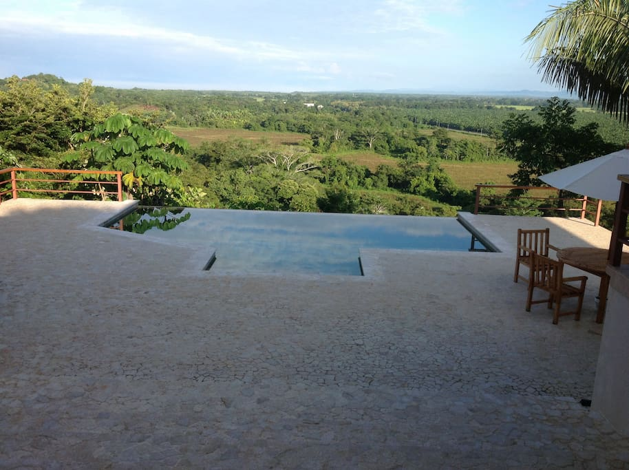 The panoramic view of the valley below and the ocean on the horizon from the outside living space