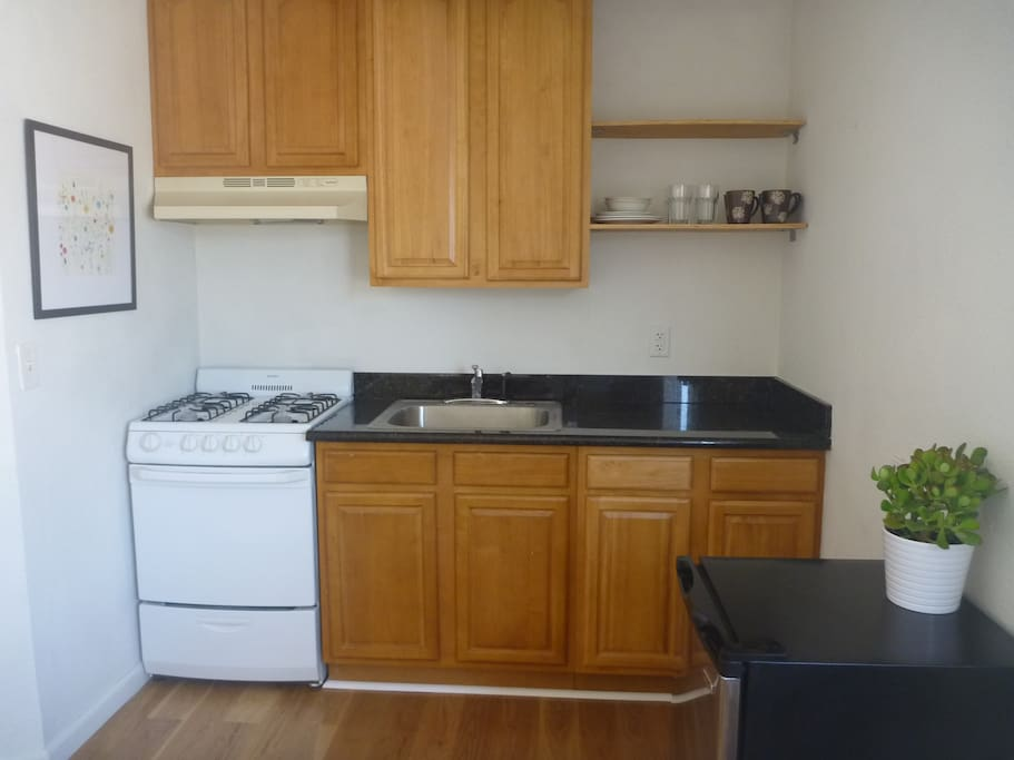 Full kitchen with granite countertops and gas stove.