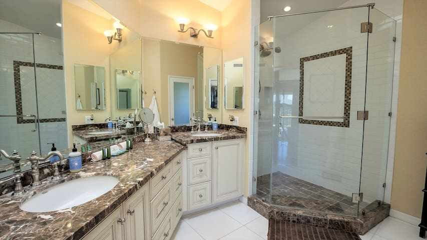 The master bathroom features his & her sinks, a walk-in shower, linens, and complimentary toiletries.