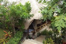 The Faery Garden Cottage with alang-alang roof nestled on the slope in the gardens.