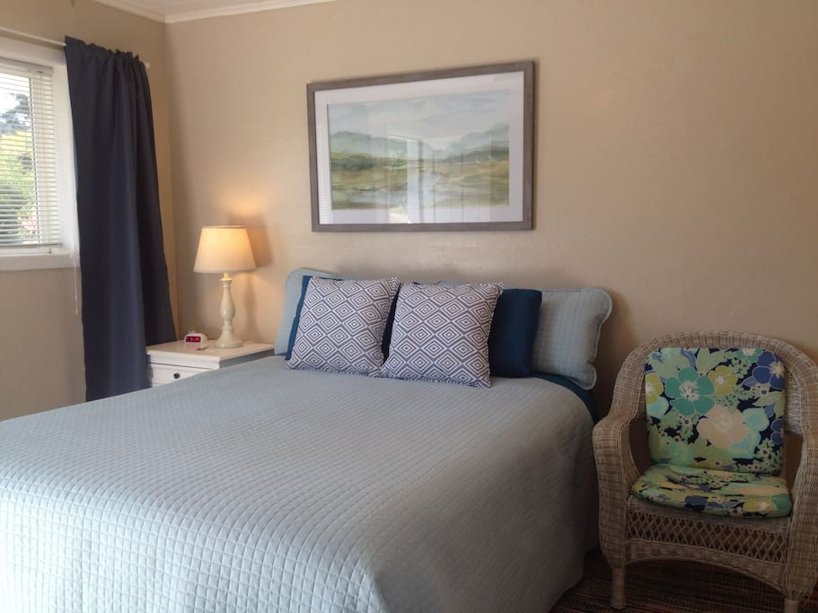 Comfy queen bed is framed by coastal art.