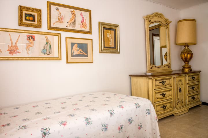 The bedroom has a full and a twin bed, original furniture with lots of storage space and a small cabinet.