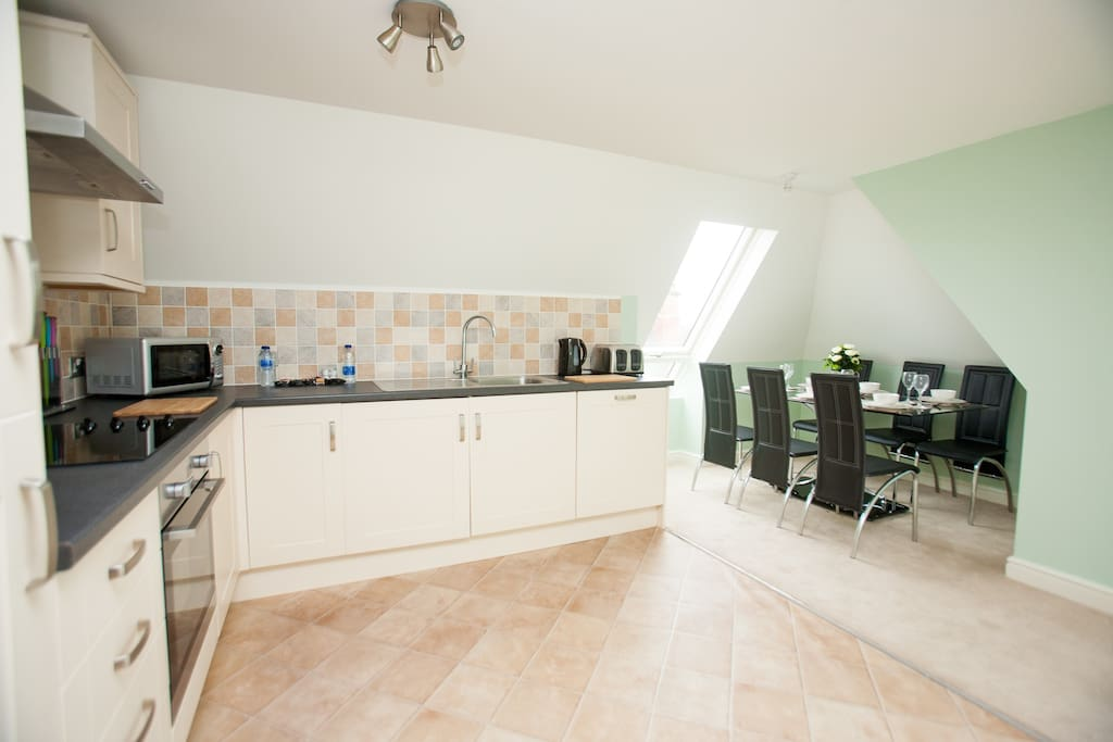 Spacious kitchen/Diner with several cupboards, washing machine, microwave, fridge/freezer, kettle, crockery, cutlery, chopping knives and board, cooking utensils and dining area.