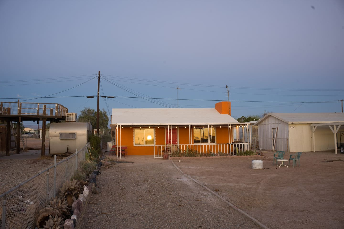 """The bright """"Orange House"""" is located on a large open yard."""