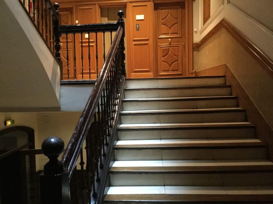 Amplia escalinata antigua de madera noble y mármol, con luminaria abovedada de luz natural en lo alto.
