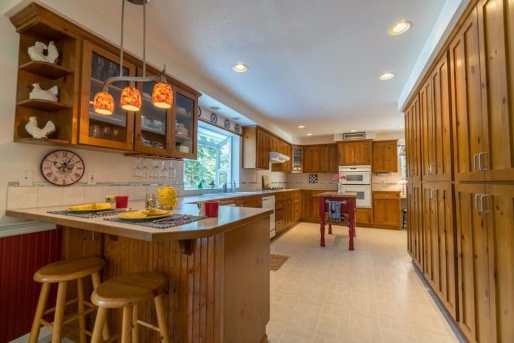 kitchen with breakfast bar, prep island, microwave, oven and toaster oven.