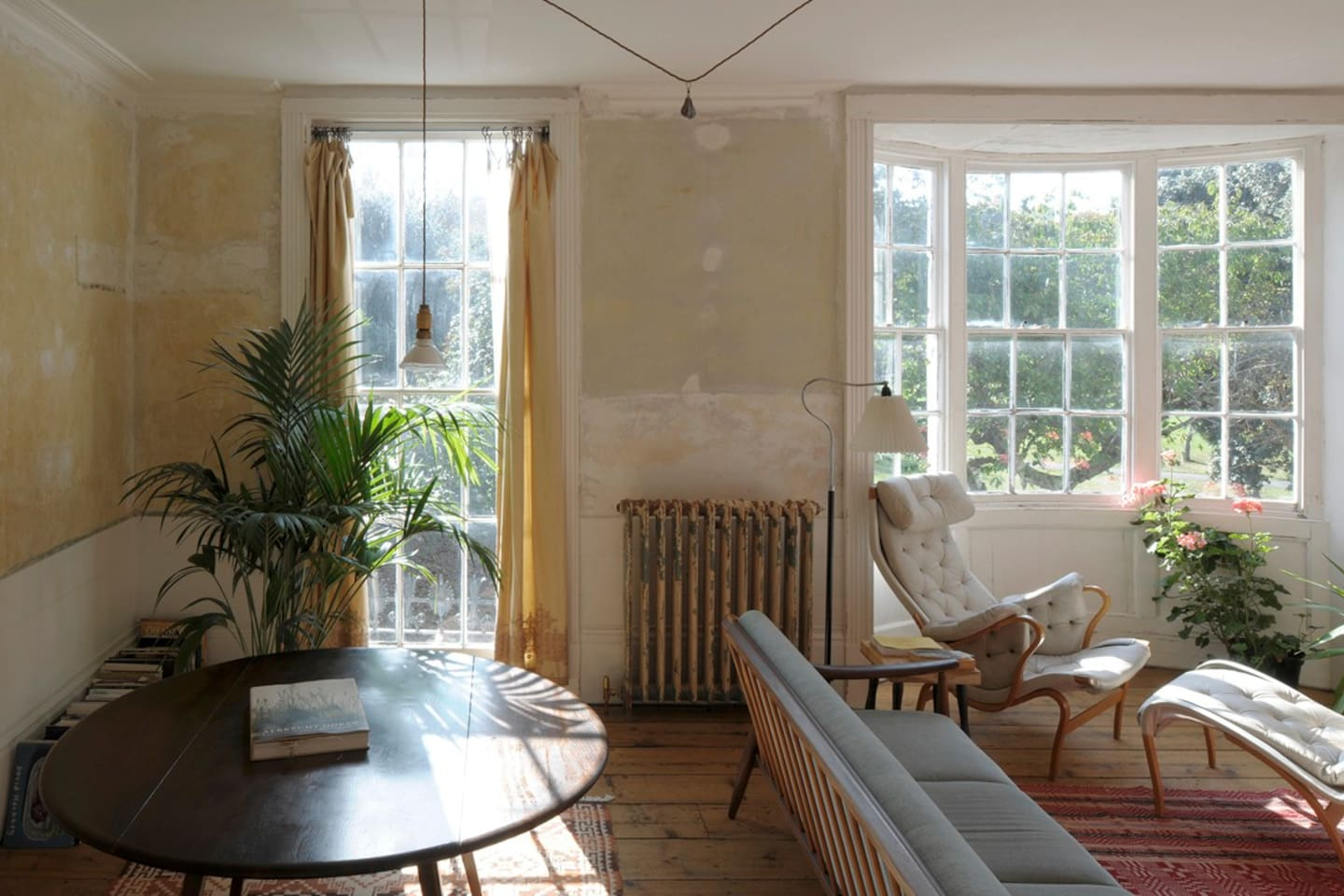 """The Sitting Room on the First Floor with comfortable sofas, a Modernist leather armchair, large bay and floor-to-ceiling window facing the very green Georgian square. The whole house has been renovated with a """"light-touch"""". We wanted to let the rich history of Margate be visible."""