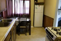Kitchen with dinner table with 4 chairs.