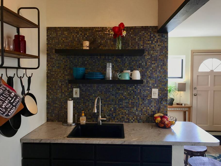 The kitchen is recently remodeled with a mosaic backsplash and breakfast bar.