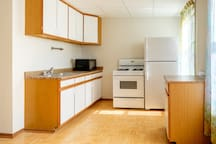 Kitchen- equipped with gas stove, coffee pot, refrigerator, and more! Plenty of space to make a wonderful meal.