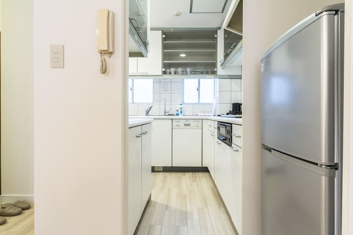 Kitchen with full sized fridge, gas stove & kettle