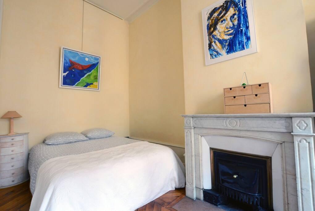 Chambre 2 avec cheminée decorative. Piece très lumineuse avec un grand placard.