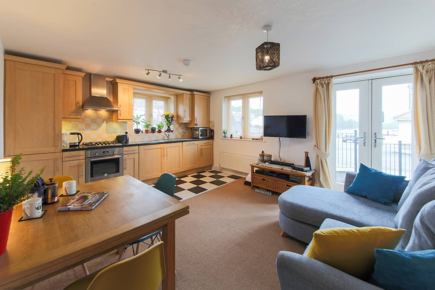 Open plan kitchen/lounge with French doors looking out onto the Carrick Roads.