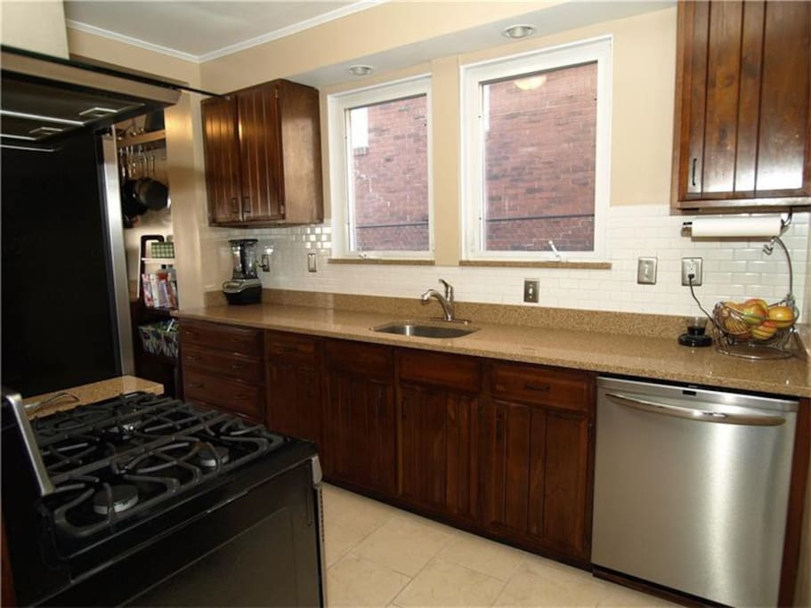 Fully equipped kitchen with gas range, dishwasher, and all cooking tools.