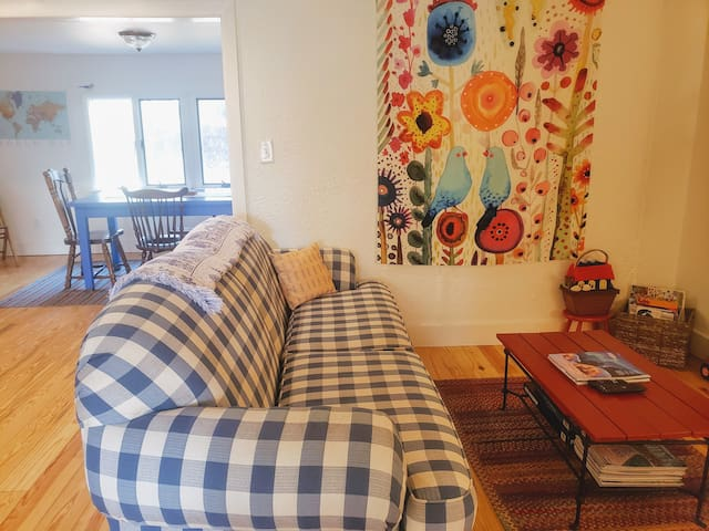 The living room has a fun wall tapestry, an LL Bean braided wool rug, and plenty of games, books, and puzzles for kids.  It is tucked just around the corner from the dining area and kitchen.