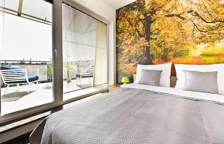 Widok na miasto z łóżka. Przeszklone ściany sypialni i salonu dają wrażenie otwartości na miasto. Nikt nie zagląda przez okna, które dają dużo światła.