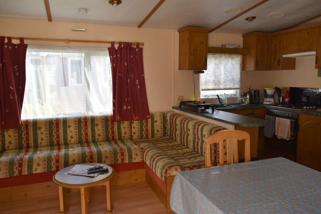 Grande pièce à vivre avec TV et cuisine fonctionnelle