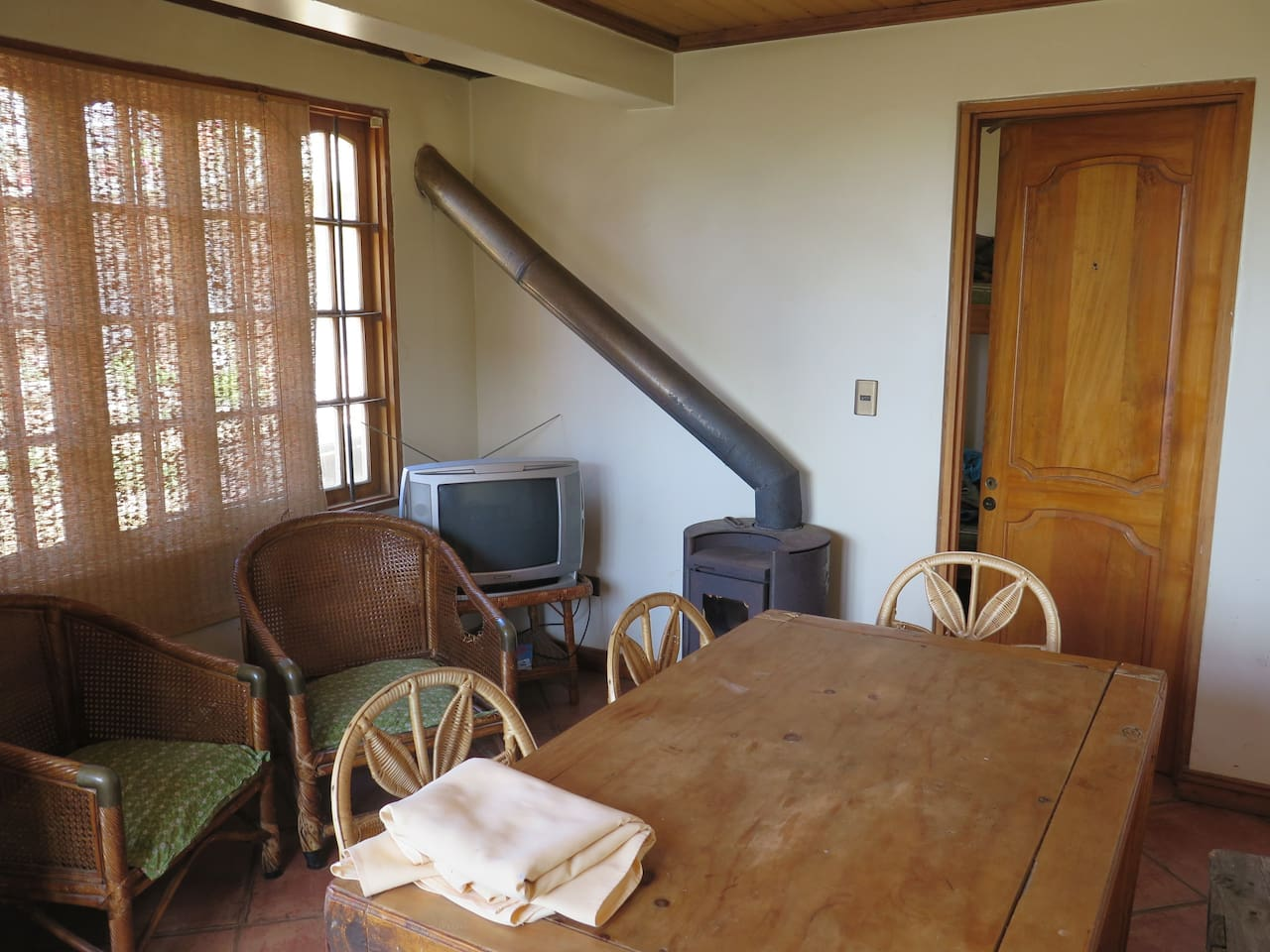 Living area with dining table and slow combustion heater for cooler nights.