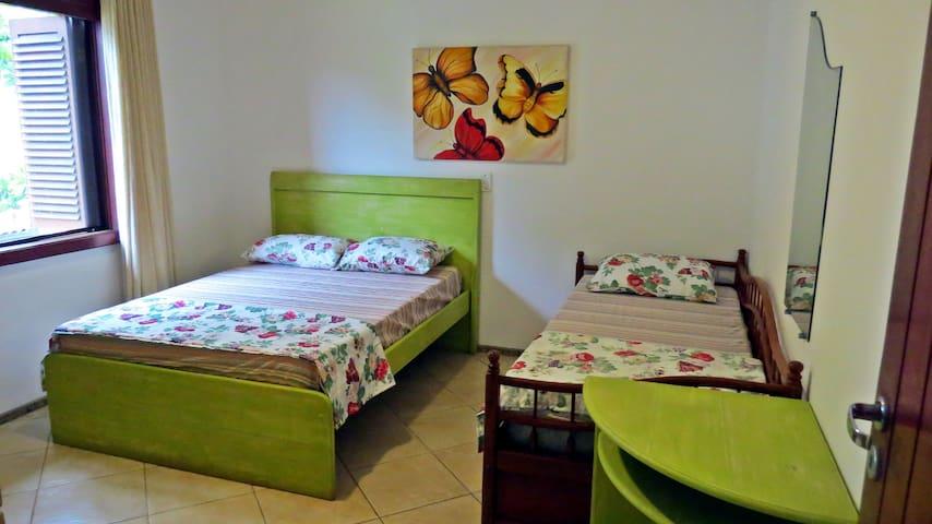 Quarto com uma cama de casal e duas camas de solteiro.