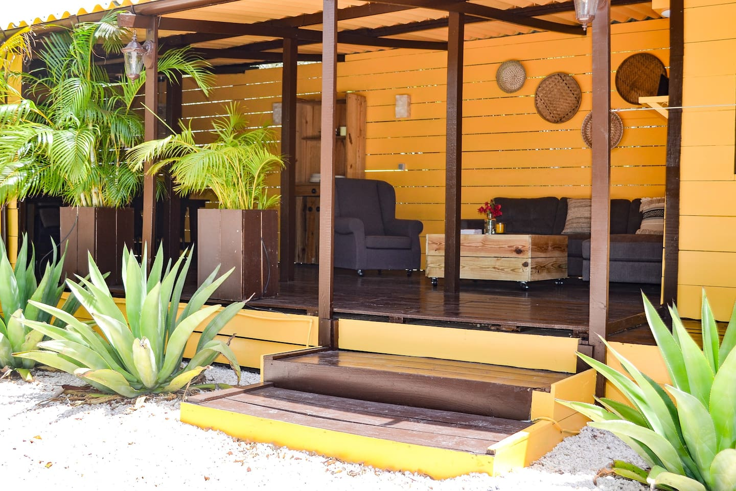 Large veranda full of shade with lounge sofa and lounge chairs. Also a large wooden diner table.