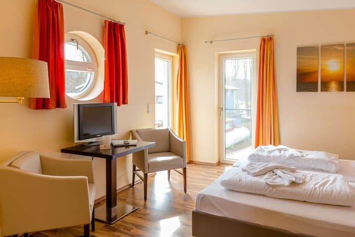 Zimmer mit Doppelbett, kleinen Tisch mit 2 Stühlen.