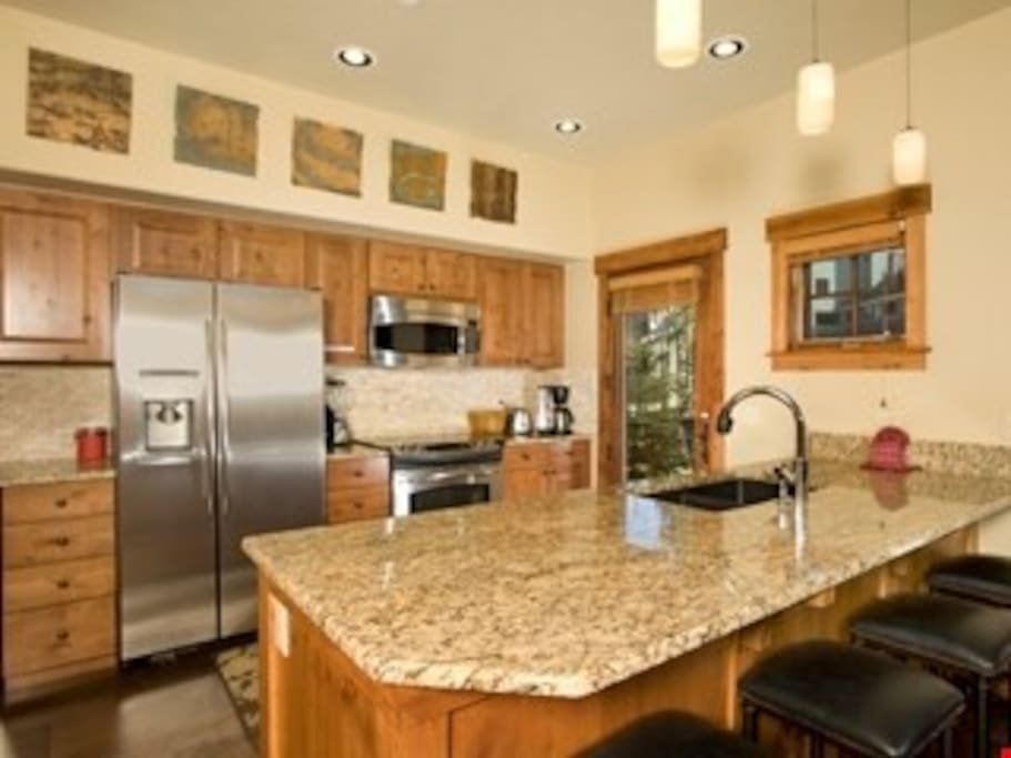 The fully-equipped kitchen features granite countertops, stainless steel appliances and a breakfast bar.