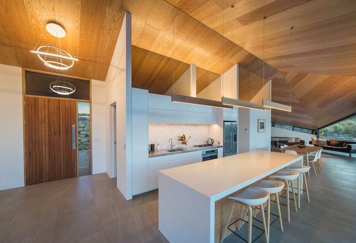 The kitchen is the hub of this 3-bedroom, 3-bathroom home. A fine place to sit at the Corian bar and gaze at the folding ceiling and wide views. Foodies love the quality European appliances, which make for memorable meals at an 8-seat dining table.